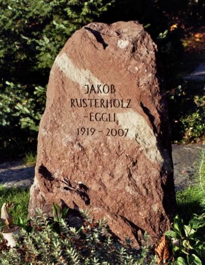 Naturbelassener Grabstein. Schlicht gehalten in rötlicher Farbe
